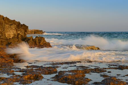 Sea evening landscape with a rocky shore and waves