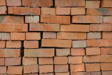Rows of red bricks laid without mortar on each other Фото со стока