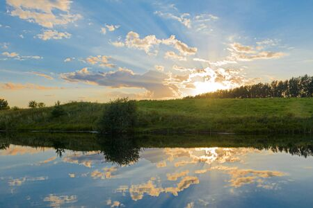 Summer evening landscape with reflection of clouds in the lake Banco de Imagens