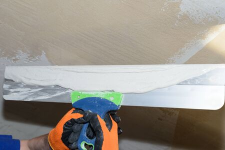 Puttying the wall with white plaster putty using a wide spatula