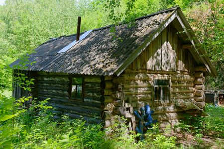 Old wooden abandoned house in the summer forest