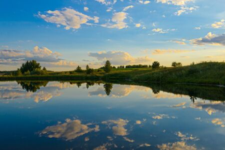 Summer evening landscape with blue sky reflected by clouds in a small lake