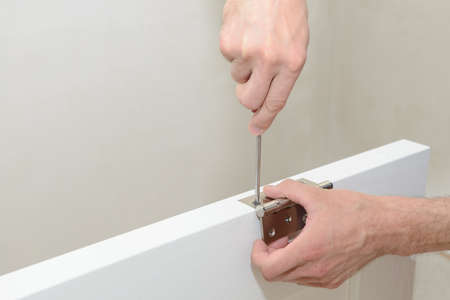 Installing the door hinge on a white door leaf