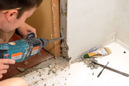 Working with a hammer to expand the doorway Banco de Imagens