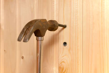 the hammer hits the dowel and hammers it into a hole in the wooden wall