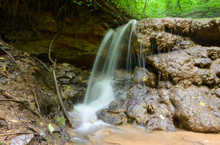Small forest waterfall on a cloudy summer day