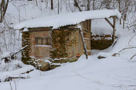 An old, crumbling hut in a winter snow-covered forest
