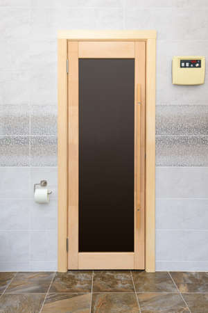 wooden door with glass on the wall made of light ceramic tiles 版權商用圖片