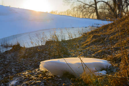 Spring evening landscape with melting snow and a small pond 版權商用圖片