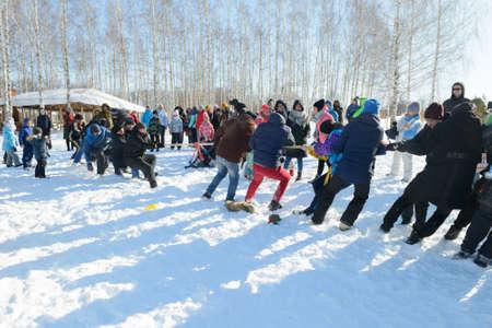 March 13, 2021: Men tug of war outside in the snow. Winter fun. Chuvashia. Russia.