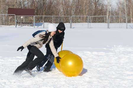 March 13, 2021: A woman and a boy roll large inflatable balls in the snow. Winter fun. Chuvashia. Russia.