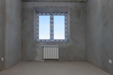 A room in a rough finish with a window and a radiator in a new building 版權商用圖片