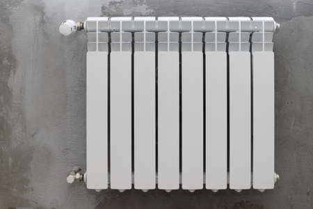 White radiator on a gray rough wall
