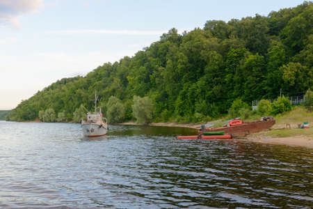 A few boats on the shore and a small ship on the river in the summer