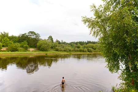 A woman in a bathing suit enters a small river on a cloudy summer day