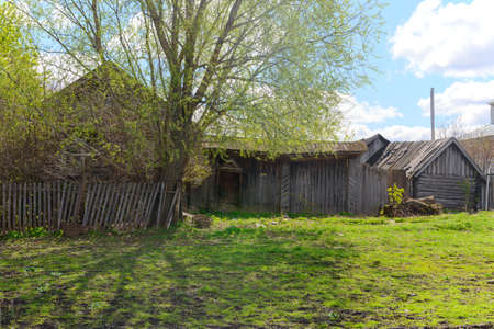 An old abandoned rickety wooden house with a gate on a sunny spring day