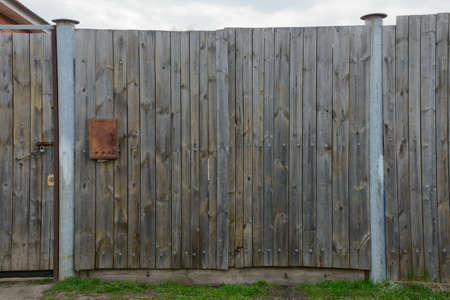 An old wooden gate with a rusty mailbox