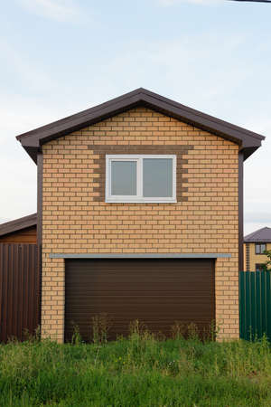 Two-story brick garage with roller shutters and a window