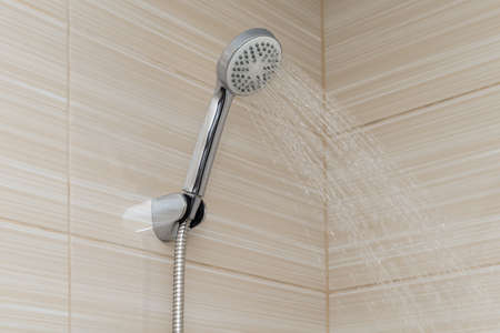 Water pours from the shower head in the bathroom with beige ceramic tiles 版權商用圖片