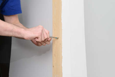 The hands of a worker in overalls twist a screw into a wooden board with a screwdriver