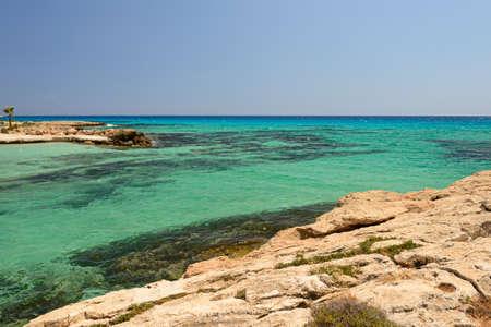 Rocky seashore in a Mediterranean resort with turquoise sea 版權商用圖片