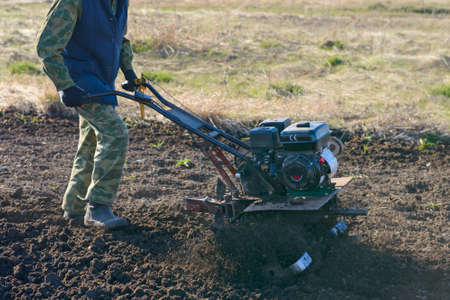 A man using a tillerblock plows the ground for planting in the spring 版權商用圖片