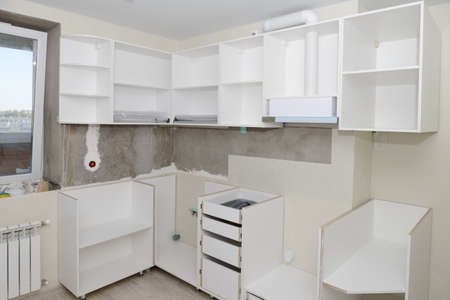 Assembly of white kitchen furniture in a renovated room 版權商用圖片