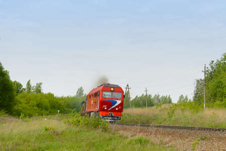 May 27, 2018: A red locomotive rides on a railway in the middle of a forest. Chuvashia. Russia.