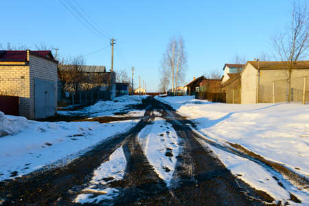 March 1, 2017: Village street with melting snow on the road. The village of Sugaikasy. Russia. 新聞圖片