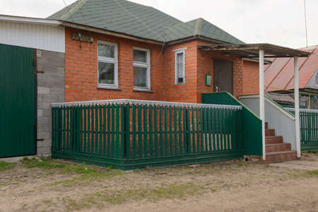 May 6, 2017: The facade of the house is made of red brick with a green fence. The village of Kivsert-Yanishevo. Russia.