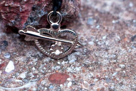 On the stones lies a metal pendant in the shape of a heart pierced by an arrow. Reklamní fotografie