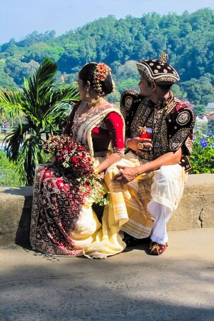 A pair of local newlyweds in Sri Lanka. Newlyweds dressed in national clothes and admire the view of the city.