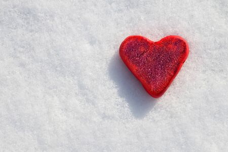 Red heart in sparkles on a white snow background.