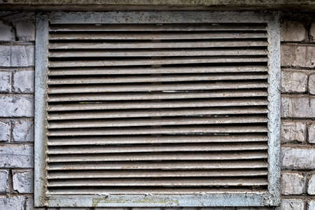 The grate of an old abandoned fume cupboard on the wall.