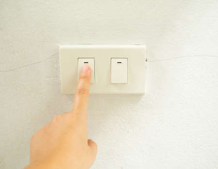 turn about: Woman hand with finger on light switch, about to turn off the lights. Closeup of hand and switch only.