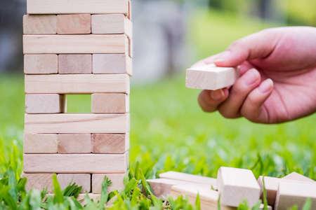 Closeup of asian womens hand playing wood blocks stack game Reklamní fotografie