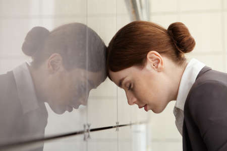 leaned: Businesswoman in fatigue leaned her head on wall