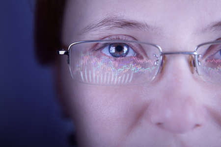 Financial advisor in glasses looking at monitor with charts