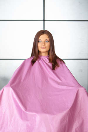 Hair salon  Young woman in hair cutting gown  photo