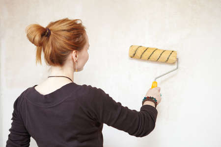 priming paint: Apartment Renovation  Young woman primed wall