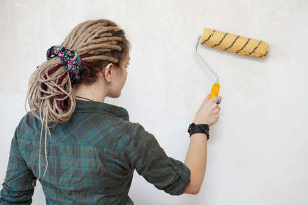 priming paint: Apartment Renovation  Young woman primed the wall
