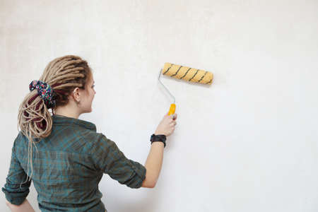 priming paint: Young woman primed the wall