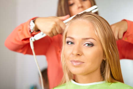 straightener: Hair salon. Women`s haircut. Use of straightener. Stock Photo