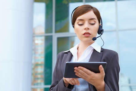 Businesswoman with headset and tablet pc. photo