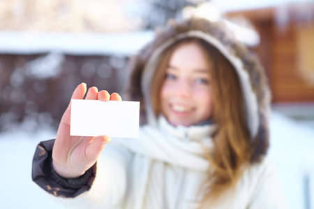 Young beautiful girl with blank visiting card. Winter. photo