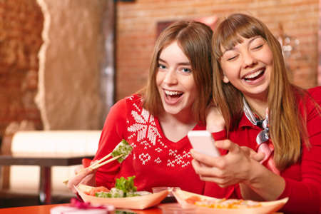 Beautiful girls eat sushi rolls at sushi bar. photo