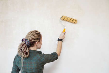 priming paint: Young woman primed the wall. Stock Photo