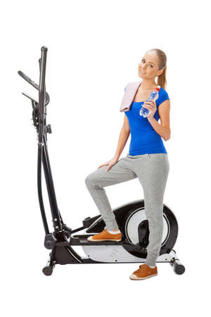 Young woman uses elliptical cross trainer. photo