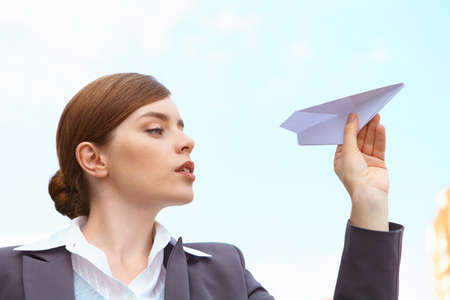paper airplane: Businesswoman launches paper airplane.