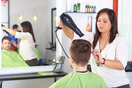 Hair salon. Men`s haircut. Use of hair dryer. Stock Photo